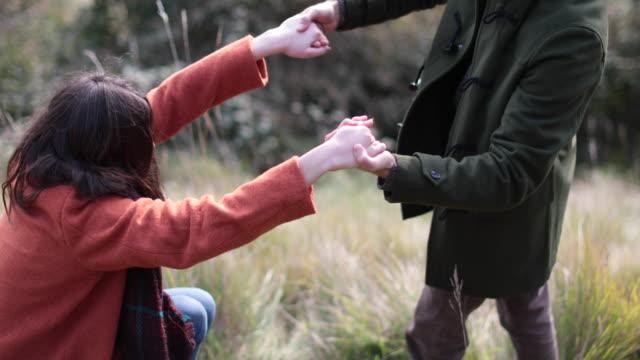 boyfriend helping girlfriend up in countryside - オーバーコート点の映像素材/bロール