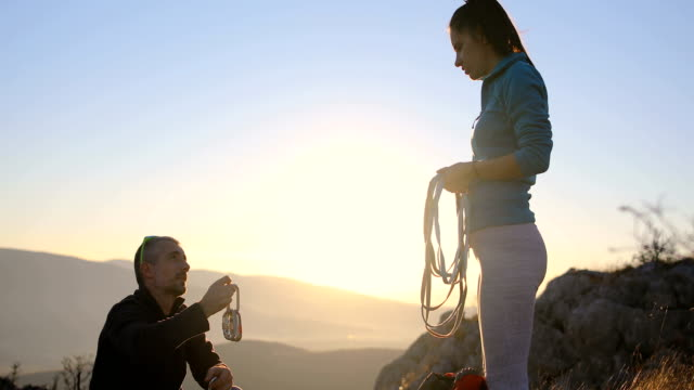 boyfriend is training his girlfriend at the top of a mountain and packing climbing equipment for a hike in the alps - climbing equipment stock videos & royalty-free footage