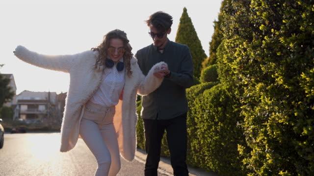 vídeos de stock, filmes e b-roll de noivo que aprende sua amiga como ao skateboarding - casal jovem