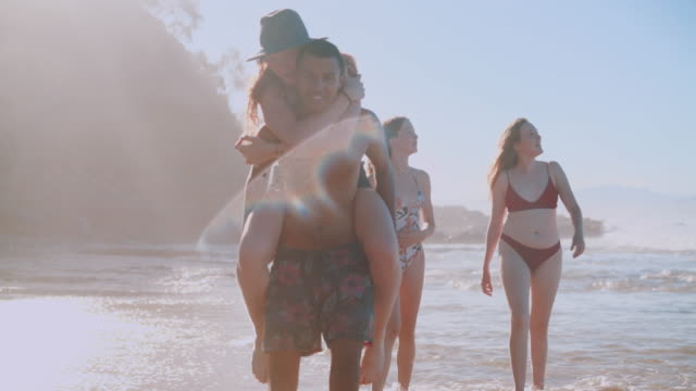 Novio piggybacking su novia en la playa