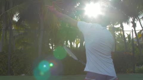 vidéos et rushes de a boyfriend playing tennis against his girlfriend while on vacation on a tropical island. - seulement des jeunes hommes