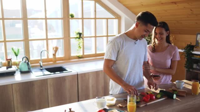 vídeos de stock, filmes e b-roll de noivo que prepara o pequeno almoço para sua amiga na cozinha - fazer