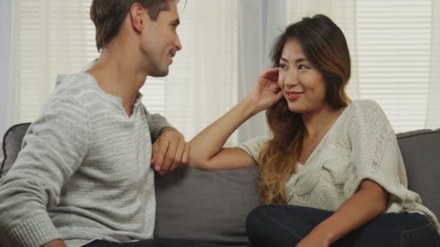 Boyfriend proposes to woman on couch