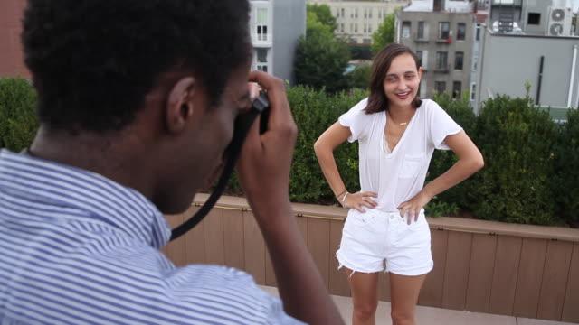 ws boyfriend taking pictures of girlfriend on rooftop - coppia di adolescenti video stock e b–roll