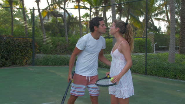 A boyfriend teaching his girlfriend how to play tennis while on vacation on a tropical island.