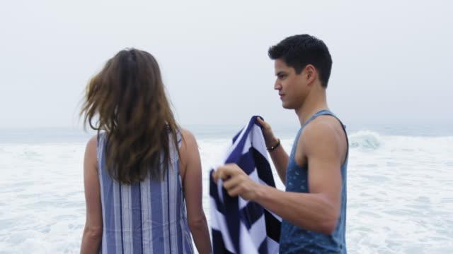 boyfriend wrapping girlfriend in towel - avvolto video stock e b–roll