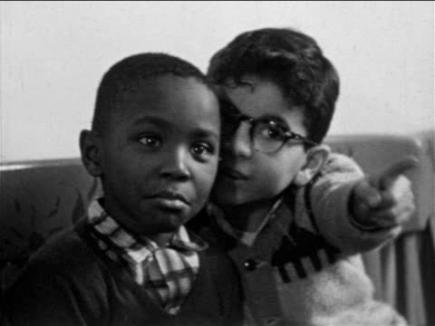 B/W 1955 2 boys, 1 Black, looking + pointing at something offscreen / Philadelphia / travelogue