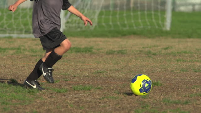 boys ages 6 to 8 playing in a youth soccer league game. - slow motion - kicking stock videos & royalty-free footage