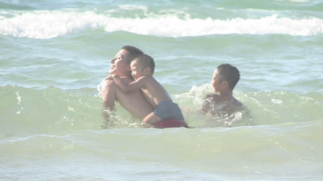 Boys and father swimming in sea