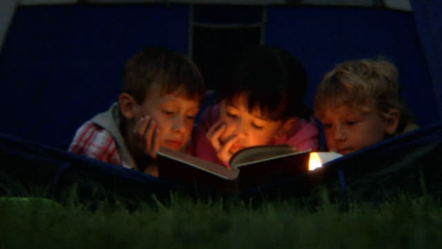 MS Boys and girl lying sitting in open tent and reading a book by flashlight/ Bovina, New York
