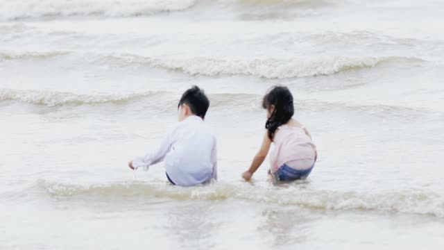 Boys and girls are playing in the sea on the beach