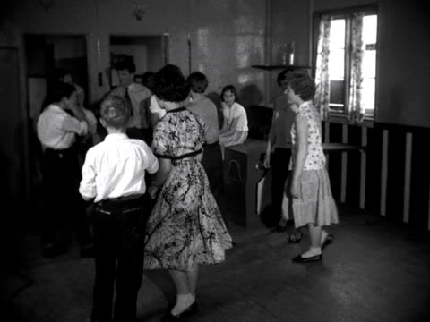 Boys and girls dance to rock and roll music inside a youth club hut 1957