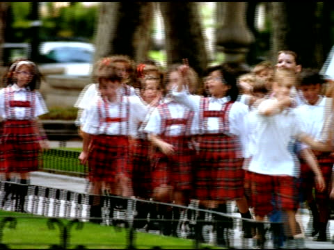 boys and girls in red tartan private school uniform walk and skip along pathway, madrid - tartan stock videos & royalty-free footage