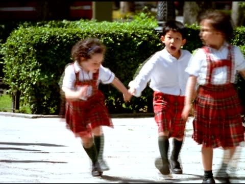 Boys and girls in red tartan private school uniform walk, run and skip along street, Madrid