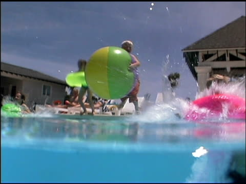 boys and girls jumping in swimming pool with colorful innertubes and giant beach ball. the viewer follows the action from above to under the water. - see other clips from this shoot 1135 stock videos & royalty-free footage