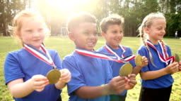 Boys and girls on sports team, showing off awards