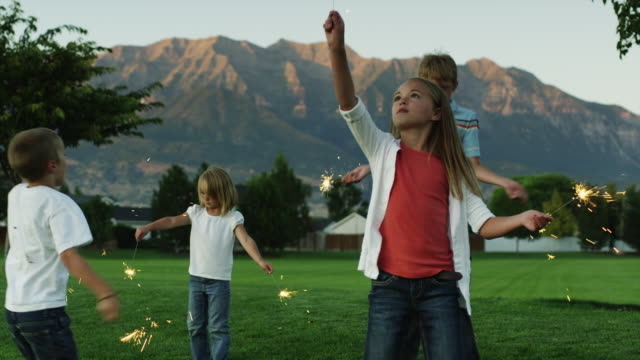 ws boys (6-7, 12-13) and girls (4-5, 10-11) playing with sparklers in park at dusk / orem, utah, usa - orem utah stock videos & royalty-free footage