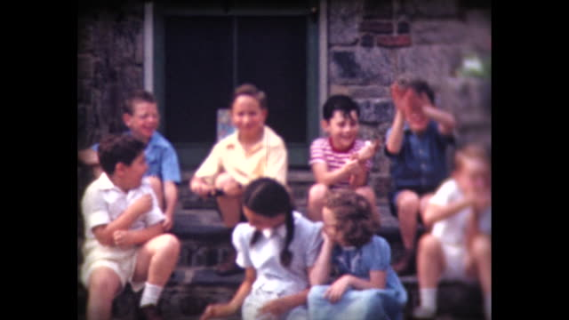 vídeos de stock, filmes e b-roll de 1942 boys and girls sitting on porch steps - home movie