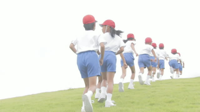 Boys and girls wearing uniforms running up hill