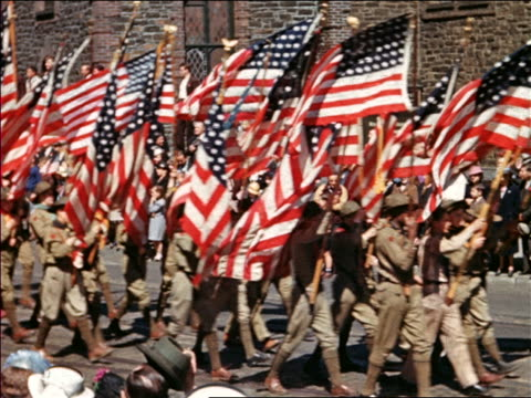 1940 boys and men in boy scout uniforms carrying us flags in parade / home movie - ボーイスカウト連盟点の映像素材/bロール