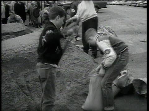 stockvideo's en b-roll-footage met boys and men sandbagging street / st paul minnesota united states - st. paul minnesota