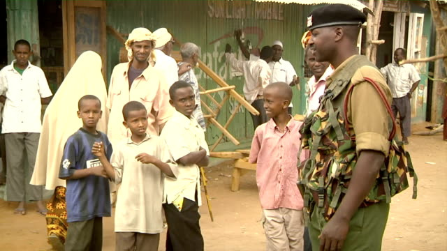 boys and soldier standing on the street on august 01 2011 in dadaab village kenya - 歩兵点の映像素材/bロール