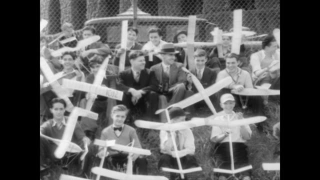 / boys and young men smiling in a group holding their model airplanes / everyone gets up at the same time and walks off to fly plane / boys fly... - 1932 stock-videos und b-roll-filmmaterial