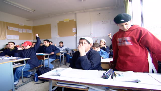 boys at their desks in a classroom, one of them stands up to speak. irfan is a druze religious school with five branches across lebanon that operate... - teenage boys stock videos & royalty-free footage