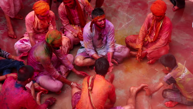 boys celebrating holi, festival of colours while colour and water is being poured on them - tradition stock-videos und b-roll-filmmaterial