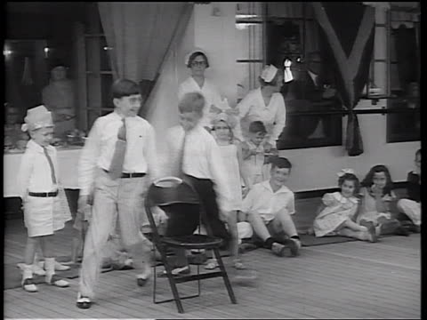 b/w 1934 2 boys circling around chair / 1 boy sitting + winning game / children + adults in background - 1934 stock videos & royalty-free footage