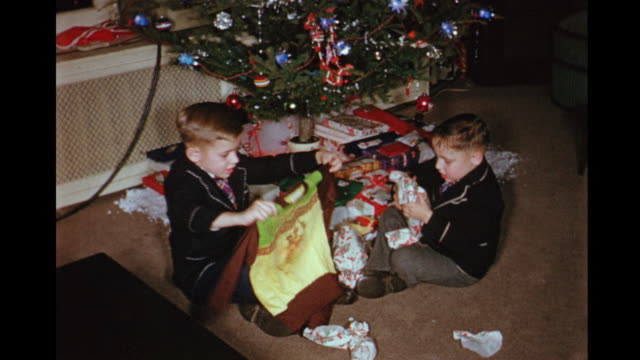 1955 home movie boys coming into living room and opening presents at christmas / toronto, canada - nostalgie stock-videos und b-roll-filmmaterial