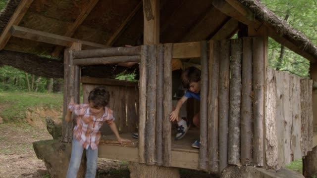 vídeos de stock, filmes e b-roll de rapazes, saindo da casa da árvore na floresta - treehouse