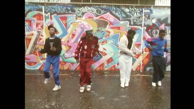 vídeos de stock e filmes b-roll de ws boys dance to rap music beside graffiti wall; 1989 - cultura hip hop