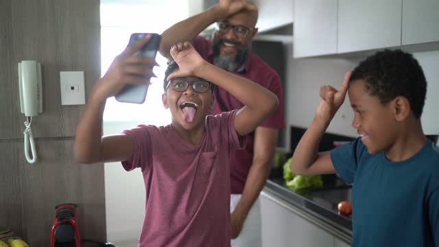 boys dancing with father at home and filming on smartphone - filming stock videos & royalty-free footage