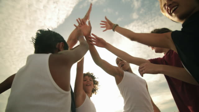 vídeos y material grabado en eventos de stock de boys doing high fives and running off on beach - 12 13 años