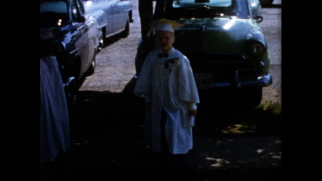 boys dressed in white cap and gown walking out of a building holding hands; walks next to parking lot and toward camera - white点の映像素材/bロール