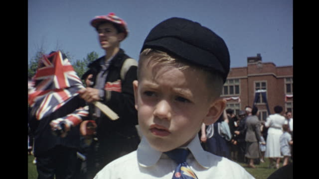 1953 home movie boys dressed up at outdoor gathering to celebrate queen elizabeth's coronation and waving union jack flags / toronto, canada - 1953 stock videos & royalty-free footage