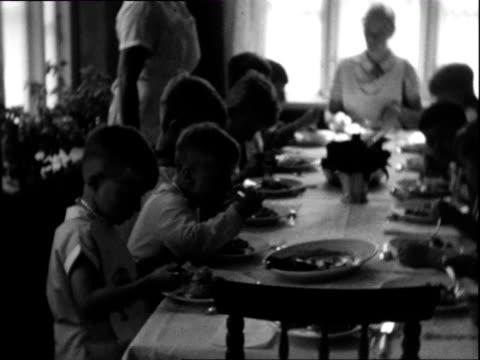 stockvideo's en b-roll-footage met 1932 b/w ms pan boys eating at table at children's summer camp / wyk auf fohr, nordfriesland, germany - gehoorzaamheid