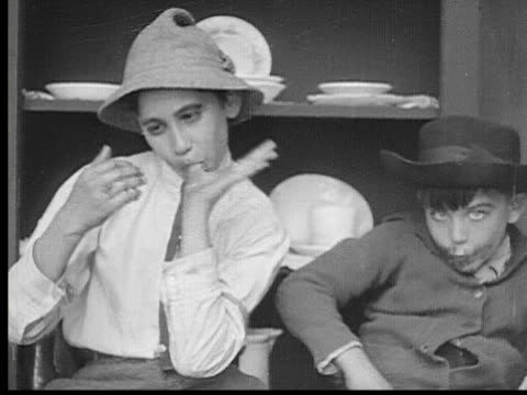 1913 b/w ms boys eating food messily and smashing plates while man (fatty arbuckle) talks to woman in next room / usa - demolished stock videos & royalty-free footage