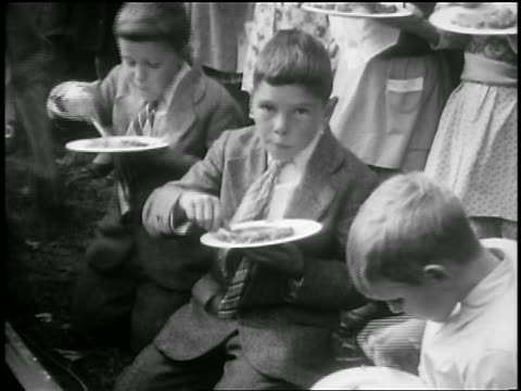 b/w 1929 boys eating slices of world's largest pie outdoors / albion, ny / newsreel - 1929 stock videos & royalty-free footage