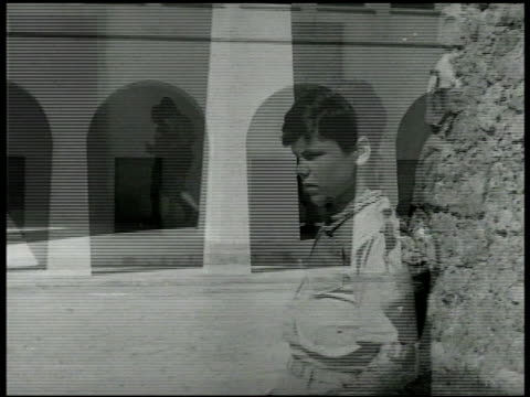 stockvideo's en b-roll-footage met boys entering school building 'carlo' watching by wall. int classroom w/ boys at desks boy writing in copy book teacher walking room. - 1946
