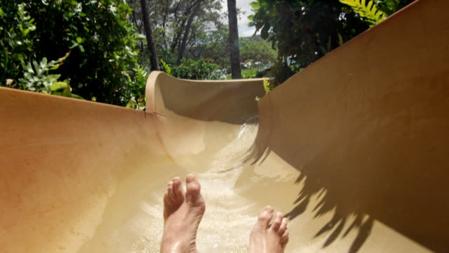 POV of boy's feet as he slides down pool slide