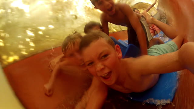 boys film themselves going down waterslide - water slide stock videos & royalty-free footage