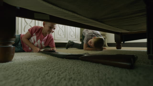 boys finding and playing with gun underneath bed / cedar hills, utah, united states - arma da fuoco video stock e b–roll