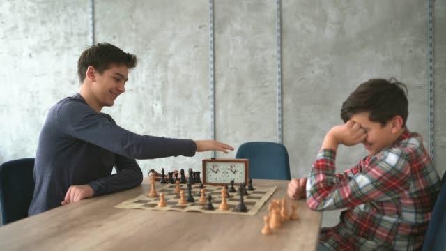 jungs beenden das schachspiel - geschwister stock-videos und b-roll-filmmaterial