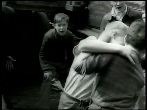 stockvideo's en b-roll-footage met boys fist fighting in alley w/ friends cheering them on policeman walking down sidewalk in low income neighborhood stopping fight holding boys apart - 1948