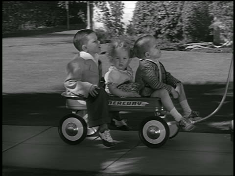 B/W 1949 PAN 2 boys + girl being pulled in wagon on sidewalk / commercial