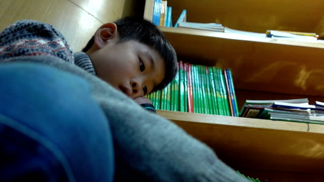 Boy's hand on chin while reading in bookstore