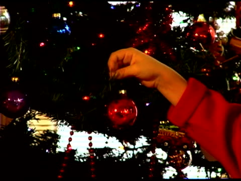 boy's hands putting ornament on christmas tree - see other clips from this shoot 1407 stock videos and b-roll footage