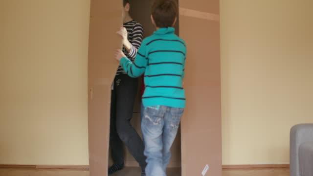 Boys hiding in cardboard box